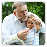 A grandfather blowing bubbles with grandson